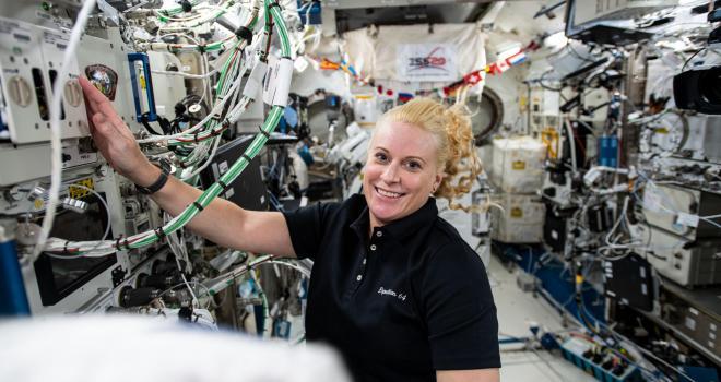 La astronauta Kate Rubins trabajando en hardware de investigación dentro de la estación espacial.