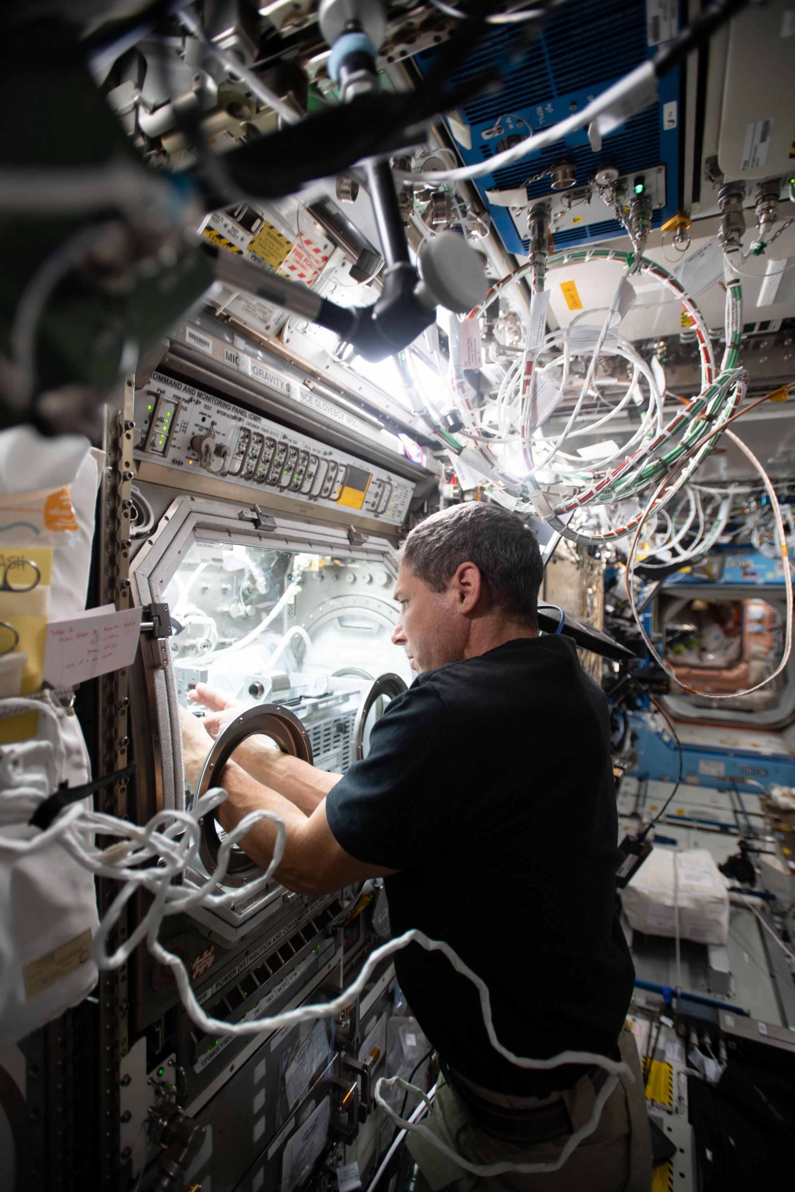 El astronauta Michael Hopkins trabaja en un experimento científico en la estación espacial