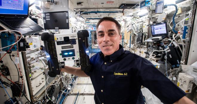 El astronauta Chris Cassidy con un astrobee flotante