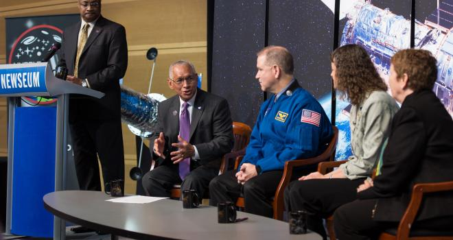 Charles Bolden sits next to three people on a stage.