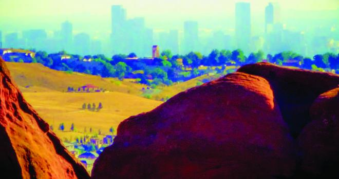 Landscape painting with city in background behind hazy sky
