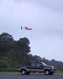 Aerosonde remote controlled aircraft above a pick-up truck it was released from