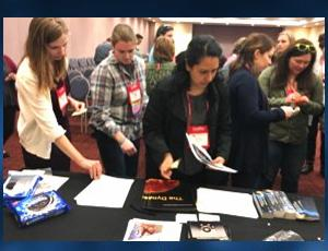Female attendees take educational materials at the NASA exhibit booth
