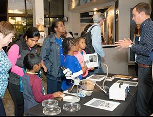A man presents to students at a display table with a microscope