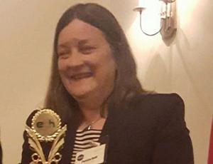 A woman holding a gold statuette award