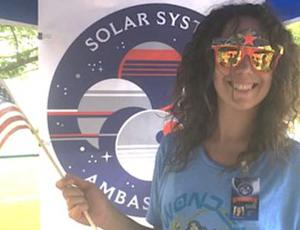 A woman wearing Wonder Woman sunglasses stands in front of an SSA display