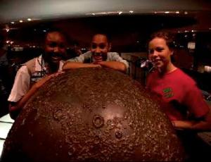 Girl Scouts leaning on large brown sphere