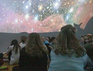 Middle school students sit in a planetarium