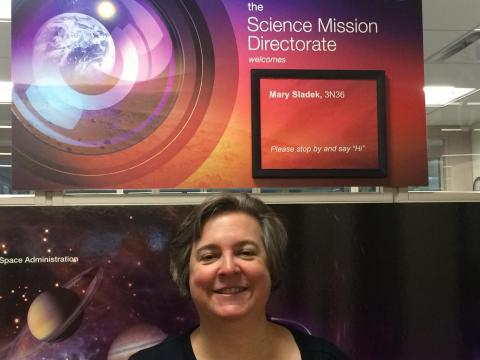 """Mary F. Sladek in front of a poster board with her name and """"Science Mission Directorate""""."""