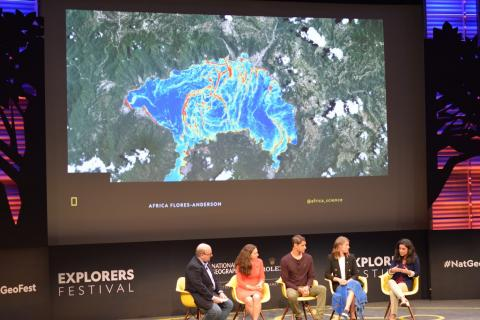 Photo of 5 scientists sitting in front of earth science data projected on screen