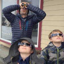 Photograph of children wearing special glasses and man with binoculars