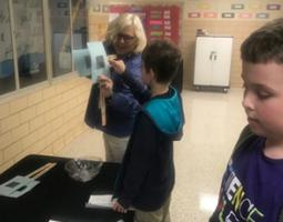 Betsy McAllister engages an elementary school student in a hands-on demonstration.