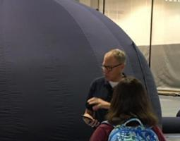 Dr. Michael Evans speaks to a student in front of a planetarium