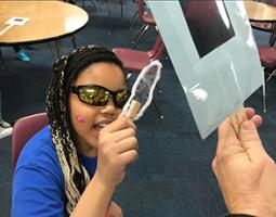 An elementary school student uses polarized sunglasses to test a plastic sample.