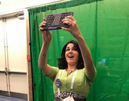 A woman takes a tablet selfie in front of a green screen.