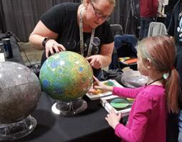 A woman and girl examine a globe.