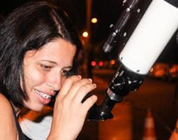 A young woman looks through a telescope