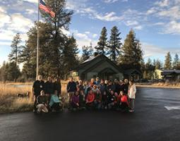 Workshop participants pose in front of a U.S. flag at Turnbull National Wildlife Refuge