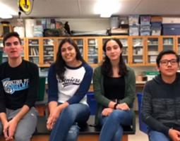 Four high school students sit in a science classroom.