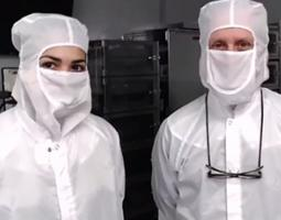 Two scientists posing in white protective clothing and masks.