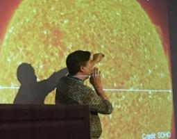 A man stands in front of a projected image of the sun