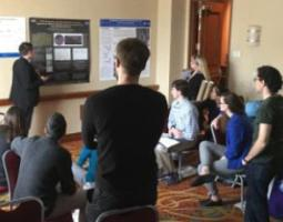 A young man presents from a poster to a group of young people