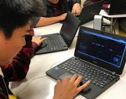 Students learning on black laptops