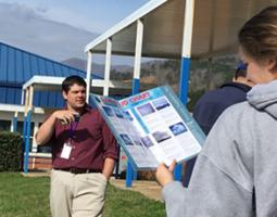 A young woman looks at a GLOBE Cloud Chart in front of a young man wearing a lanyard