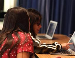 A young girl points at a laptop screen for another girl.