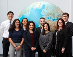 The DEVELOP team standing in front of a poster of the globe