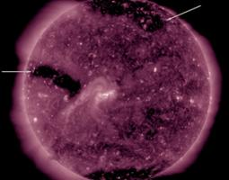 Three coronal holes appear as large dark areas which are identified with arrows in the still image.