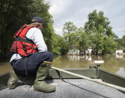 Photo of many in boat on flood waters