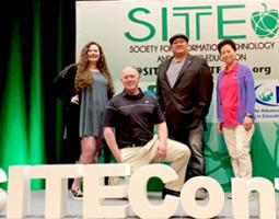 Troy Cline, Carolyn Ng, Lani Sasser, and Eddie Gonzales pose on a state in front of a SITE banner.