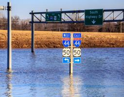 Photo of flood waters submerging highway road signs