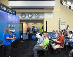 Infiniscope team member presenting Infiniscope learning experiences and teaching network on Hyperwall display within NASA booth. Audience seating filled with interested librarians.