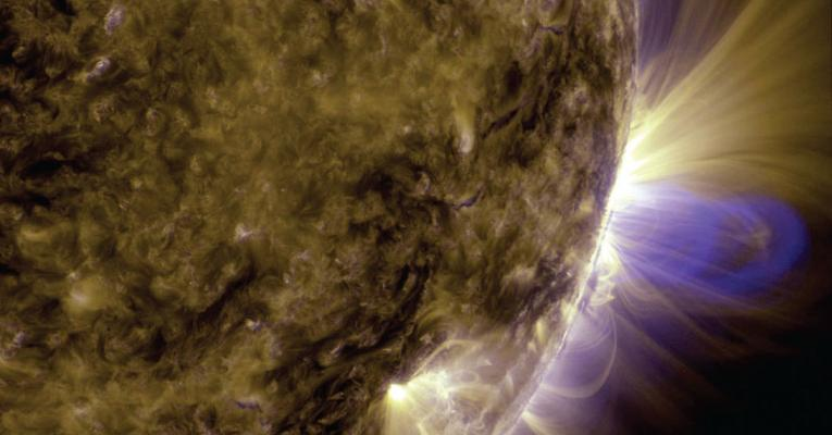 Image of colorful loops shooting out of the sun.