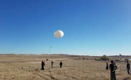 Photo of people releases weather balloons into blue sky