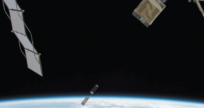 Photo of CubeSat over Earth's horizon taken from the ISS