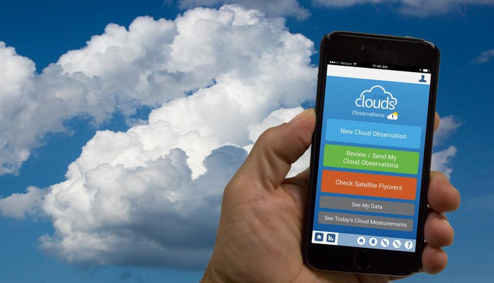 Image of handing holding mobile device with sky and clouds in background