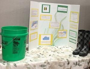 "High school research project called ""Are Farms to Blame?"" consisting of a green bucket and posterboard"