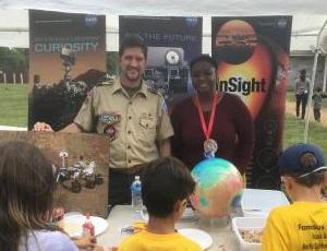 A man and woman present a Mission to Mars booth to cub scouts