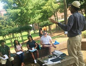 A man teaches a few students outside