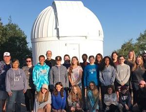 A group of people pose with the Catalina Station in the background