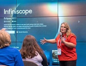 A blonde woman in a red NASA shirt gives a presentation