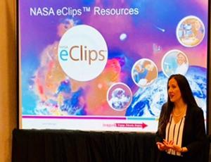 """Stacy Dees presents in front of a projector screen that reads """"eClips"""""""