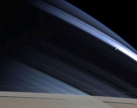 Photo of blue streaks that are Saturn's rings with a small moon in orbit nearby