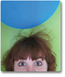 A photo of a balloon above Hannah's head. Static electricity causes her hair to raise 2-3 inches toward the balloon.