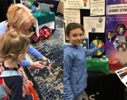 Left: Sharon Bowers demonstrates an app to a young girl. Right: Girl with her finger on a spinning multicolored wheel at an exhibition booth.
