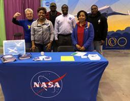 Six people pose behind a NASA display table.