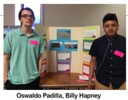 Two high schoolers pose in front of their project.